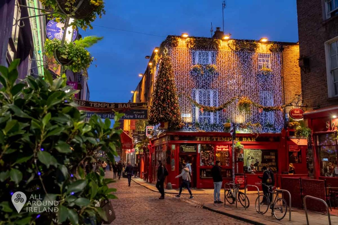 The Christmas lights of the Temple Bar shine during blue hour in Dublin