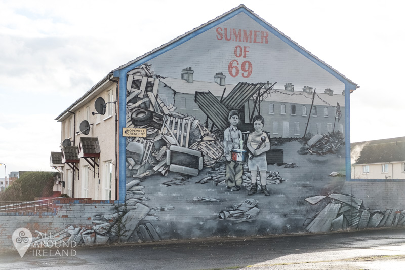 Mural of two young boys surrounded by rubble. Text at the top of the wall reads Summer of 69.