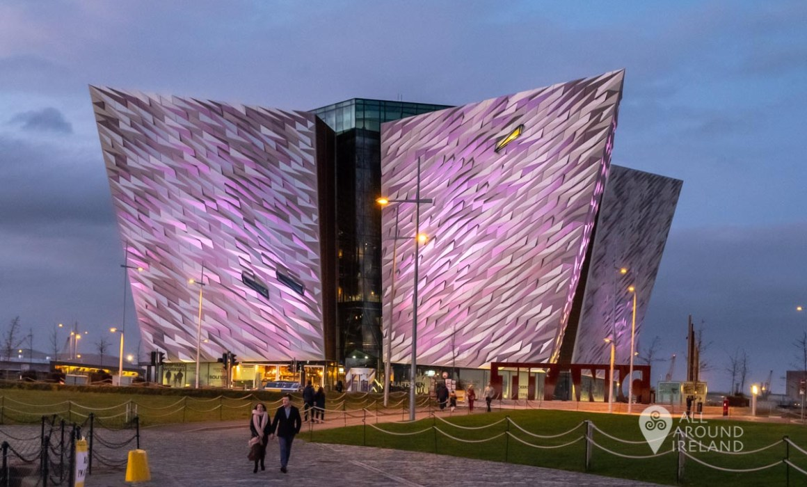 A couple walk in front of the Titanic Belfast building lit up in pink at dusk