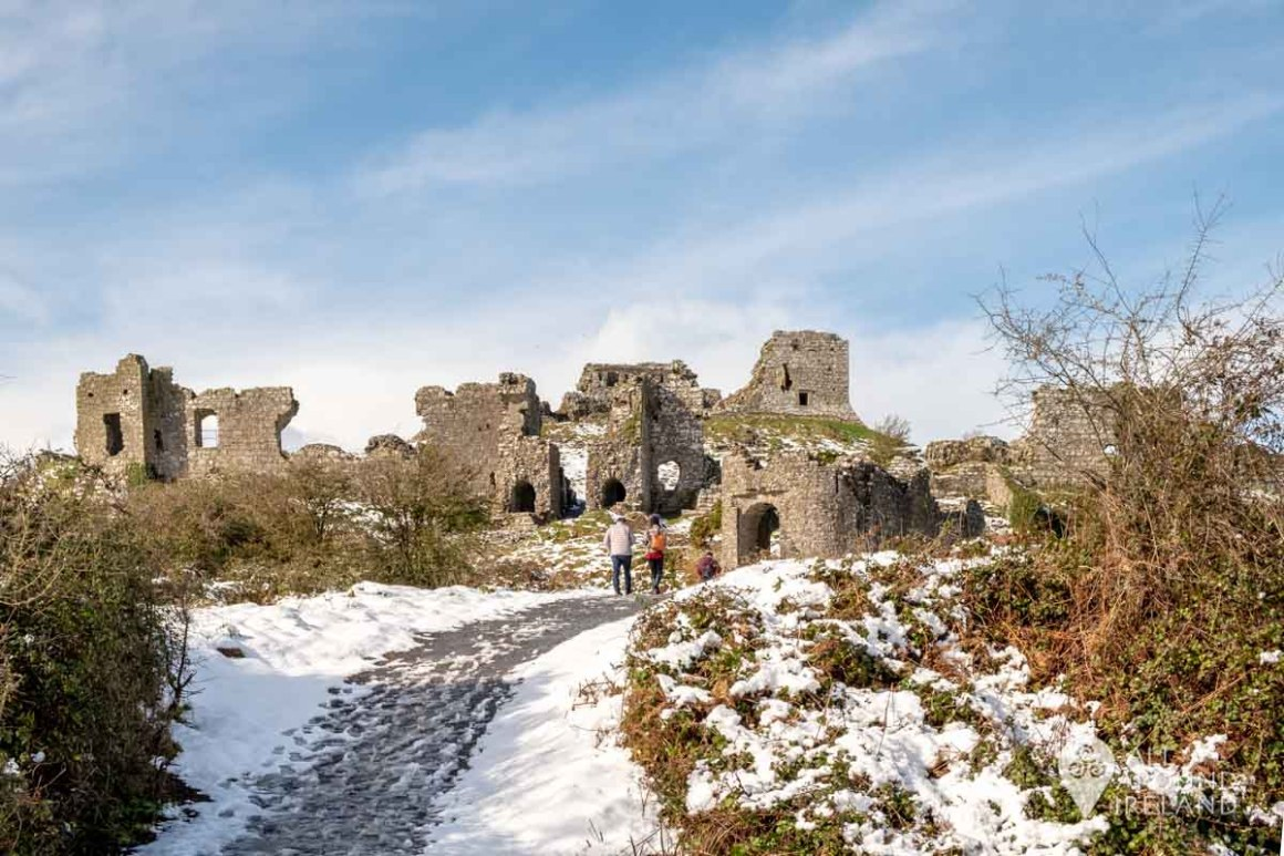 A couple walk uphill towards the ruins of Dunamase Castle