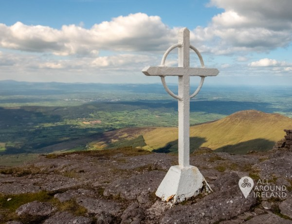 A white iron celtic cross placed on the rocky summit of Galtymore. Beyond is a stunning colourful view of the Glen of Aherlow and fluffy clouds floating overhead in the blue sky.