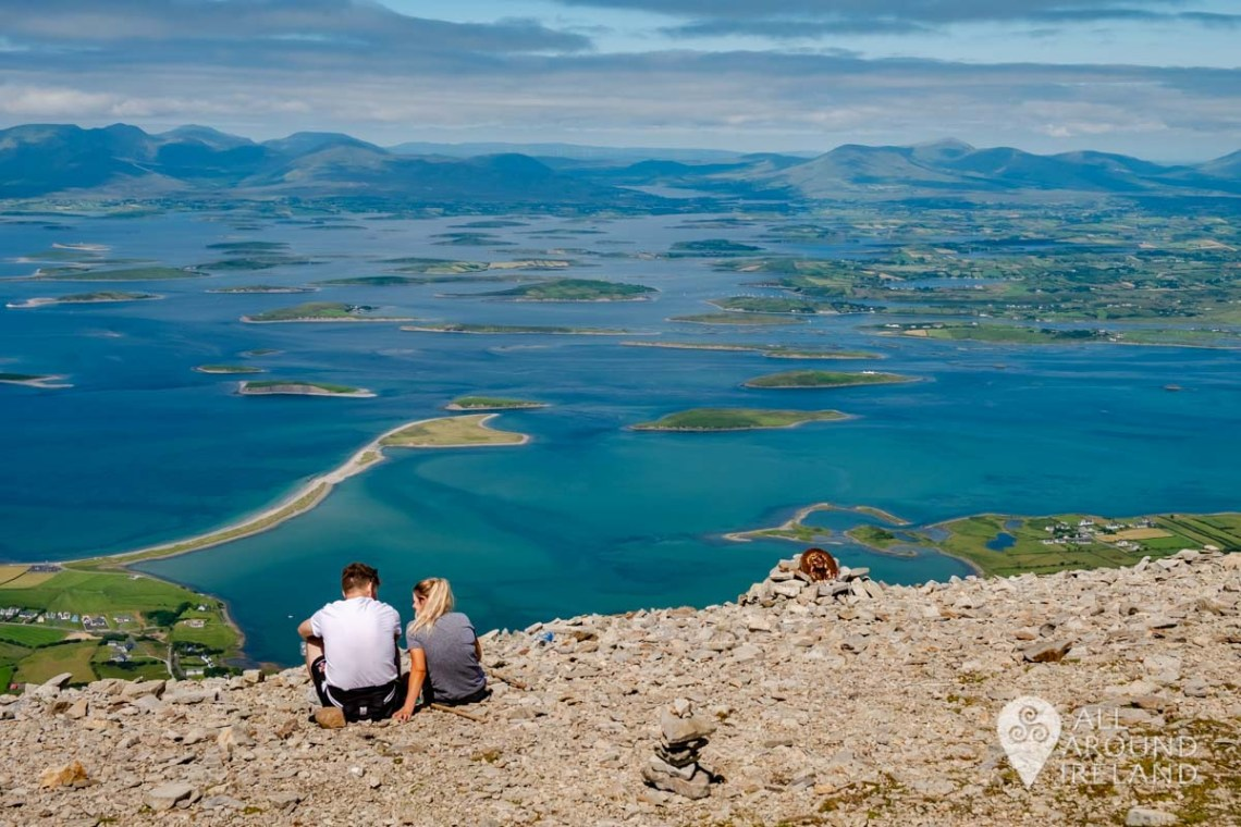 A couple sit at the summit of Croagh Patrick facing stunning views of Clew Bay on a sunny day - unique things to do in Ireland
