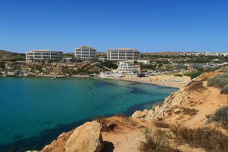 Der Sandstrand und die Klippen an der Golden Bay im Norden von Malta. Der Strand ist goldgelb gefärbt, oberhalb des Strandes steht ein großes Hotel.