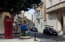 Das Bild einer Straße in der ein Bus für den Flughafentransfer steht. Daneben ist ein typisches Auto aus Malta mit dem Lenkrad auf der rechten Seite.