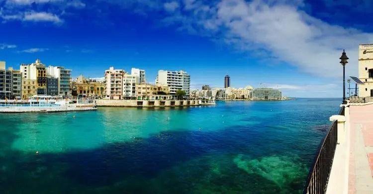 Das türkisblaue Meereswasser, gesehen von der nahen Küstenpromenade im Norden der Insel Malta. Der Blick geht auf das Meer und die auf die andere Seite der Bucht gelegenen Häuser.