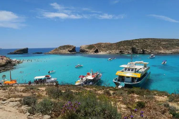 Der Blick auf die vor Anker liegenden Schiffe in der Blauen Lagune an der Insel Comino in Malta. Darin sind öffentliche Fähren und Ausflugsschiffe zu sehen.