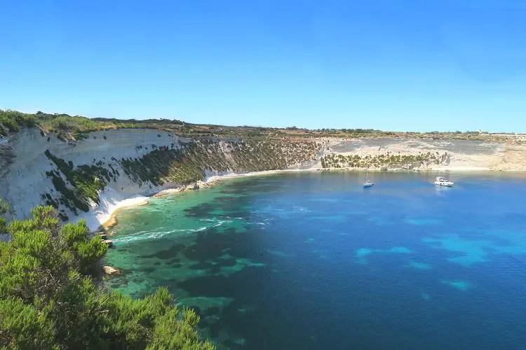 Die Bucht Il-Ħofra ż-Żgħira ist vom einer steilen Klippe umgeben. Auf dem Bild sieht man unterhalb der Klippen einen schmalen Sandstrand. Das Meer ist türkisblau gefäbrt, in der Bucht liegt eine Yacht vor Anker.