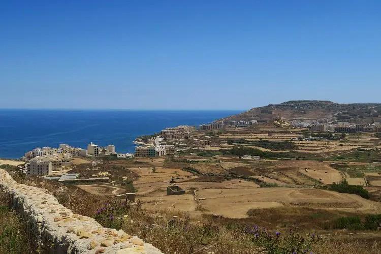 Blick vom auf einen Hügel liegenden Ort Zebug auf den am Meer gelegenen Ort Marsalforn auf Maltas Nachbarinsel Gozo. Im Hintergrund ist das Meer zu sehen.