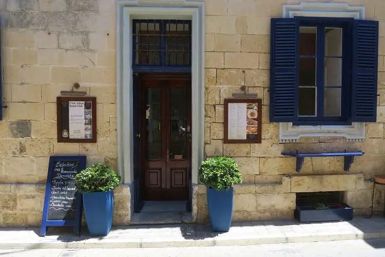 Die aus sandfarbenen Backseinen bestehende Wand eines Restaurants, mit einer kastanienfarbenen Tür und Blauen Fensterläden.
