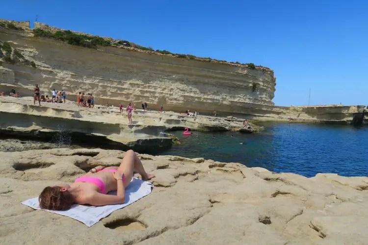Eine Frauf liegt am St. Peter´s Pool auf Malta auf den Steinen neben dem Meer.