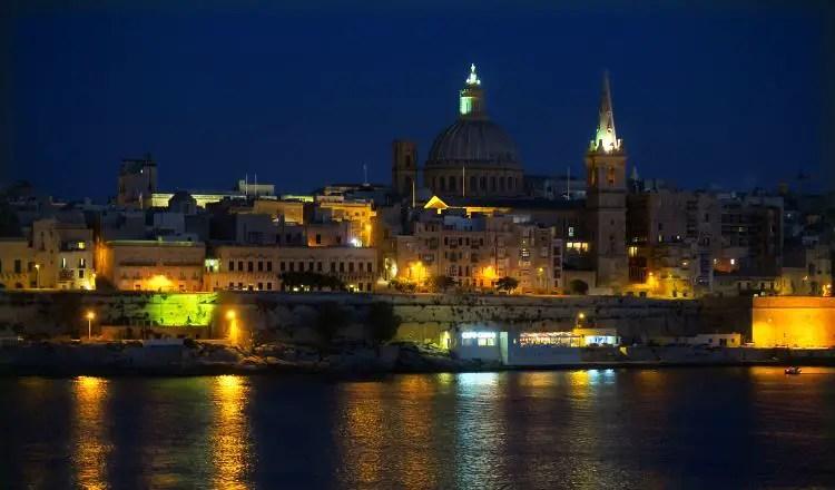 Blick von Sliema über den Marsamxett Hafen auf die hell erleuchteten Straßen in Valletta in der Nacht.