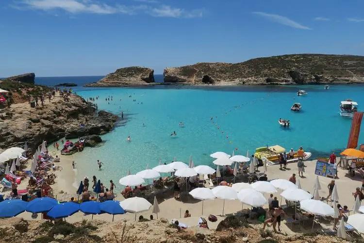 das türkisblaue, flache Meer in einer geschützten Badebucht mit vielen Badegästen.