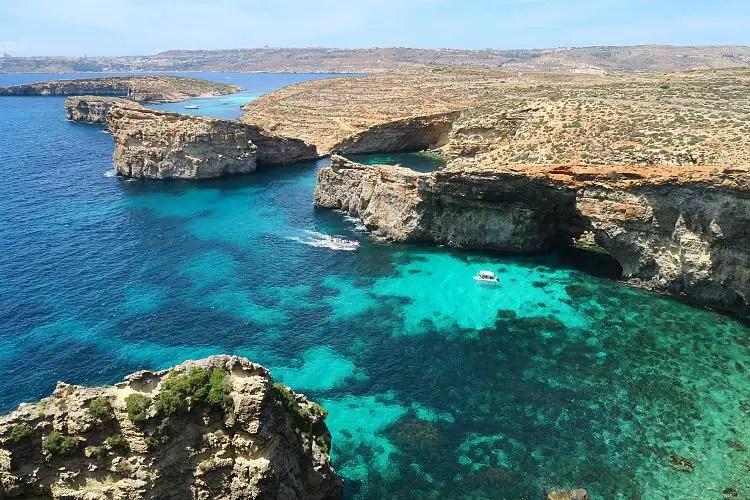 Blick von den rund 100m hohen Klippen im Süden von Comino auf das türkisblaue Meer und die Insel Gozo im Hntergrund.
