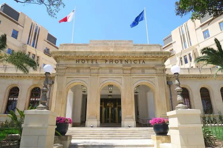 Der große Eingang des Hotels ist in schlichten, weißen Marmorfarben gehalten. Daneben weht die Falagge von Malta und der EU.