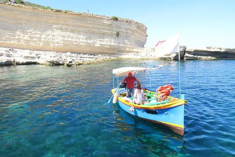 ein buntes Luzzu Boot in blau-elb-roter Farbe fährt zum St. Peter´s Pool.