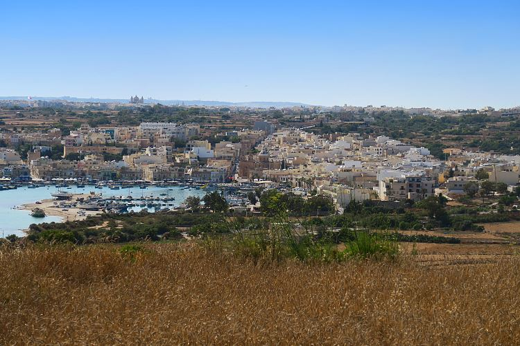 Die Stadt Marsaxlokk und der Hafen, von einem nahen Hügel aus gesehen.