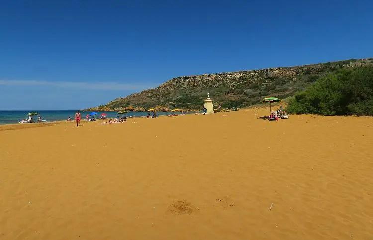 Ein großer rötlicher Sandstrand in einer Bucht.