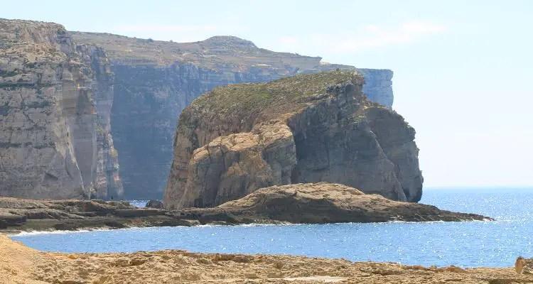 Fungus Rock an der Küste von Gozo mit den 200m hohen Klippen der Insel im Hintergrund