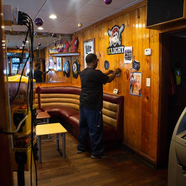 Jamie Younger working inside Young Brothers Bar. Photo: Njaimeh Njie
