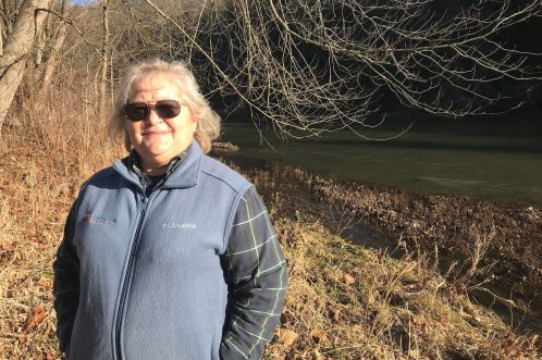 Lisa Hollingsworth-Segety, director of river restoration for American Rivers, has been involved in the removal of more than 75 obsolete dams in Pennsylvania, where she's based. She stands in front of one of those removal locations along Slippery Rock Creek in the Beaver River watershed. (Photo by Julie Grant/The Allegheny Front)