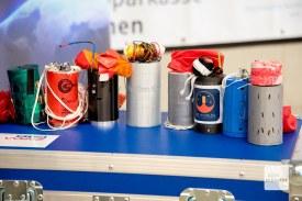 Die selbstgebauten Satelliten der acht teilnehmenden Gruppen. Der CamSat aus Münster ist der zweite von links (Foto: Bührke)