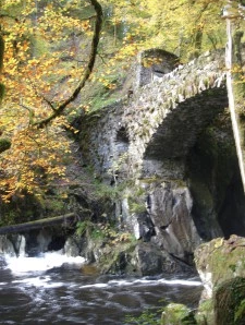 Stone bridge over falls in autumn