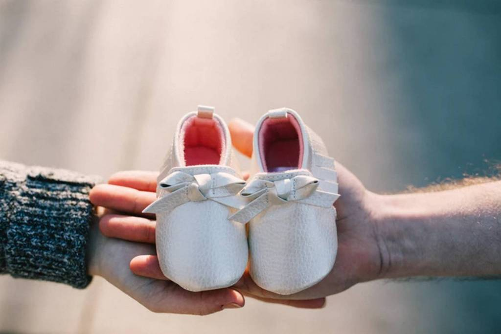two hands holding a pair of baby shoes