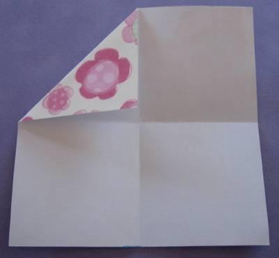 Folding the corner into the centre of the square.