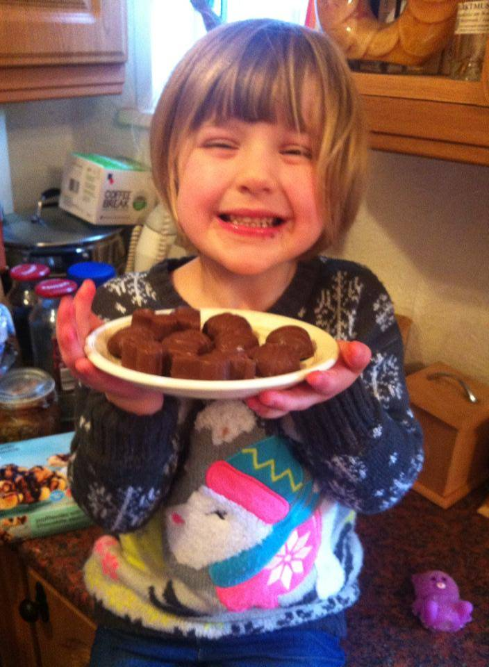 girl presents a plate of homemade chocolate Easter eggs and bunnies
