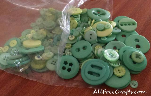 open bag of assorted green buttons