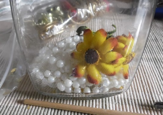 string of pearls in the bottom of a glass jar