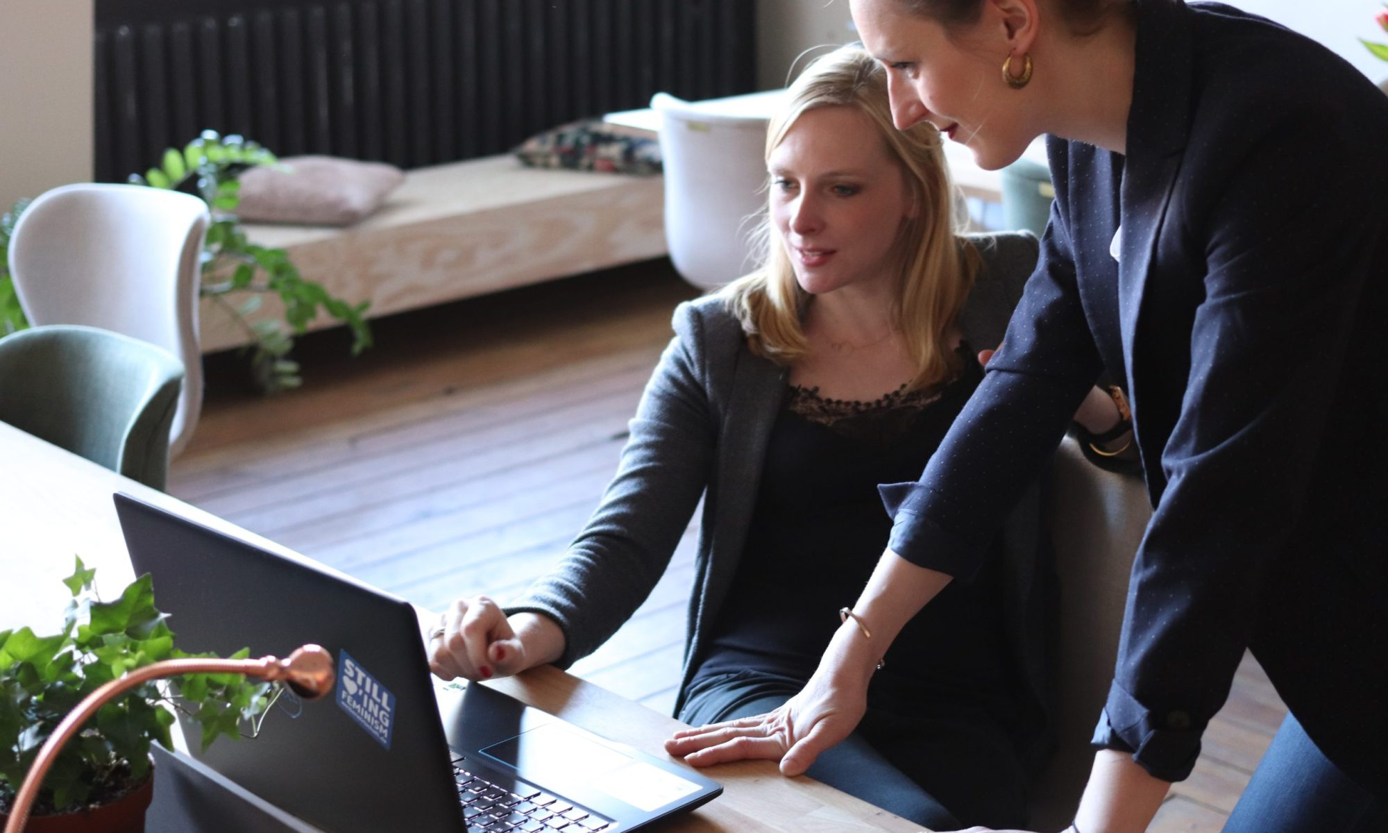 women working together at a computer copywriting for therapists