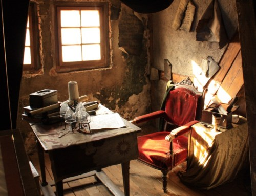 reconstruction of Edward Kelley's study near a window with candle, desk, velvet upholstered chair and sideboard with goblet