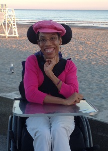 Allison is in her wheelchair on the beach at sunset. Sand is behind her and beyond the sand is the ocean. Over Allison's right shoulder is a seagull and a white lifeguard chair.