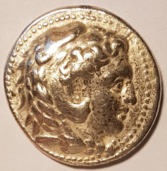 Alexander the Great as Heracles in his lion's head is shown on the obverse side of the coin.