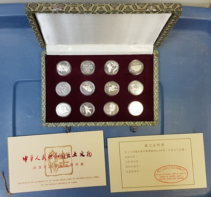 Case open showing medallions with certificates in front.