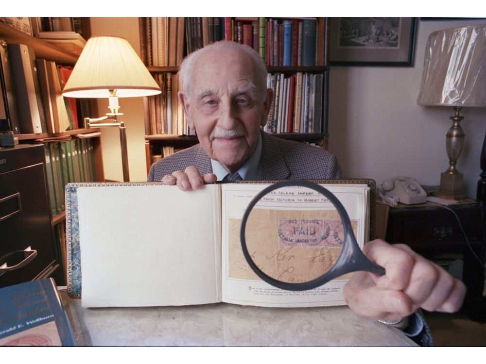 Gerald Wellburn holds magnifier to stamp