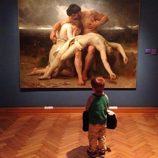 A young boy stands and ponders a dramatic work of art.