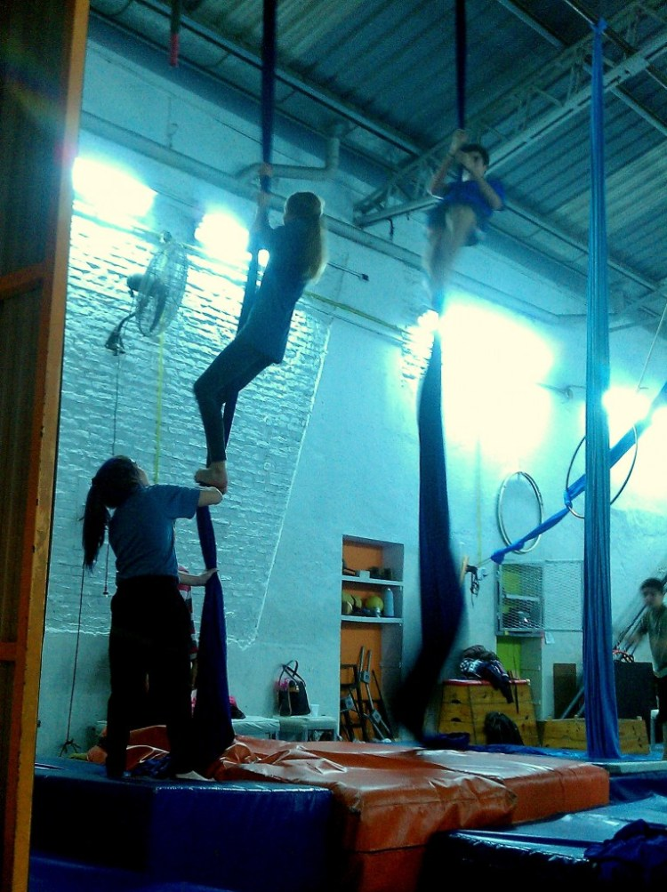 A girl on the silks in aerial acrobatics class in Buenos Aires.