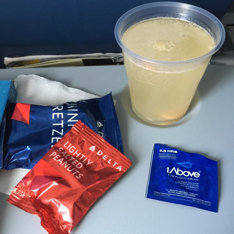 A packet of 1Above jet lag cure on an airplane tray table.