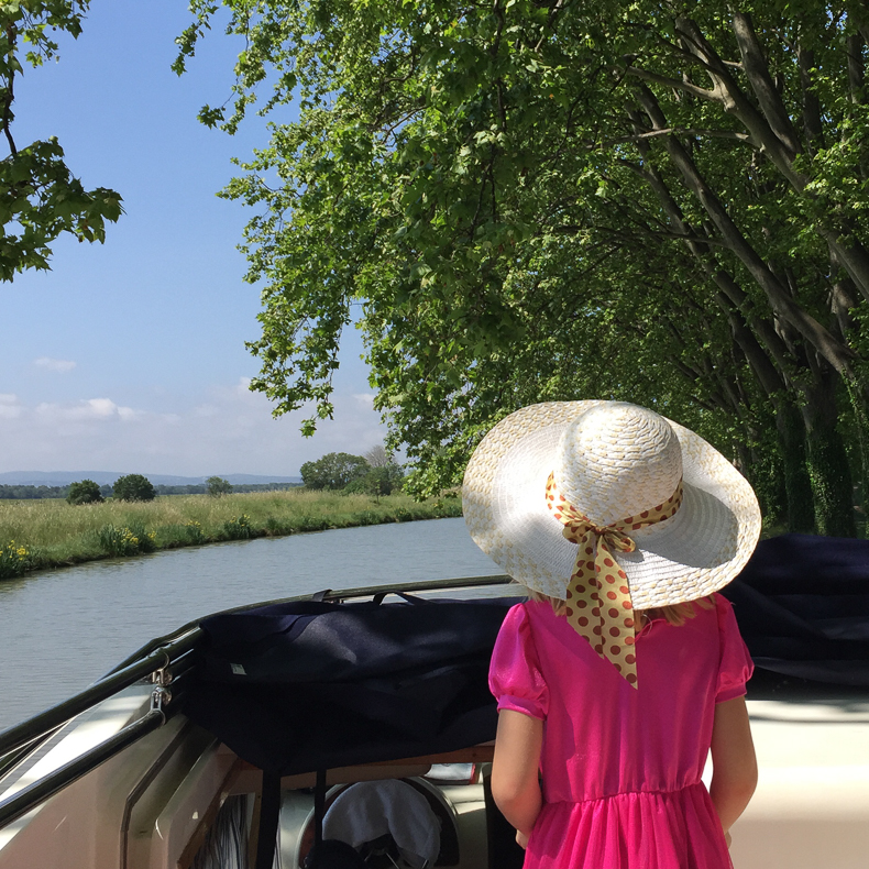 A girl in a hat in France, on a boat