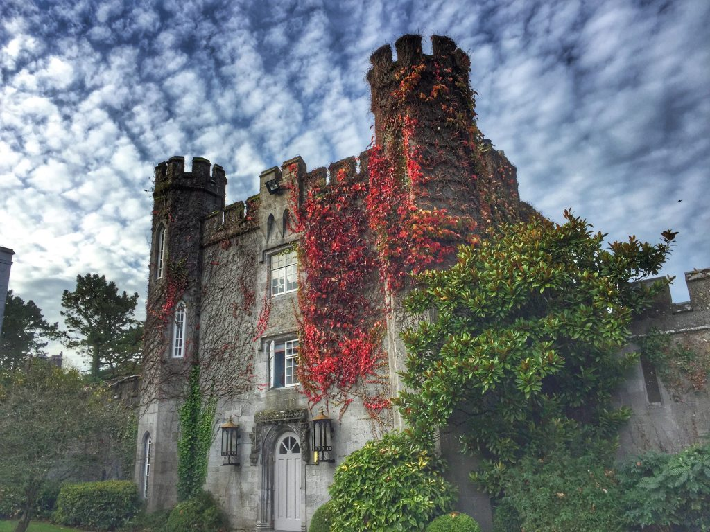 Dromoland Castle facade covered by red ivy with a cloudy blue sky above - Castle Hotels in Ireland