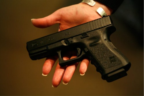 A woman holds a Glock 19, a 9 mm semi-automatic handgun.