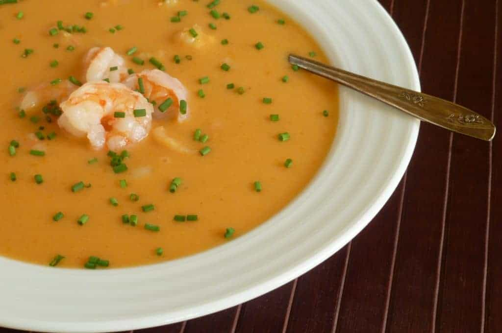 Shrimp bisque in a white bowl garnished with shrimp and chives
