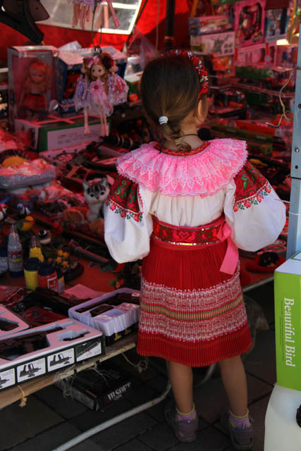 a girl in folk costume looks at cheap toys