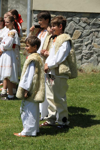 Boys in traditional sheep wool vests bake as they wait for their turn to perform