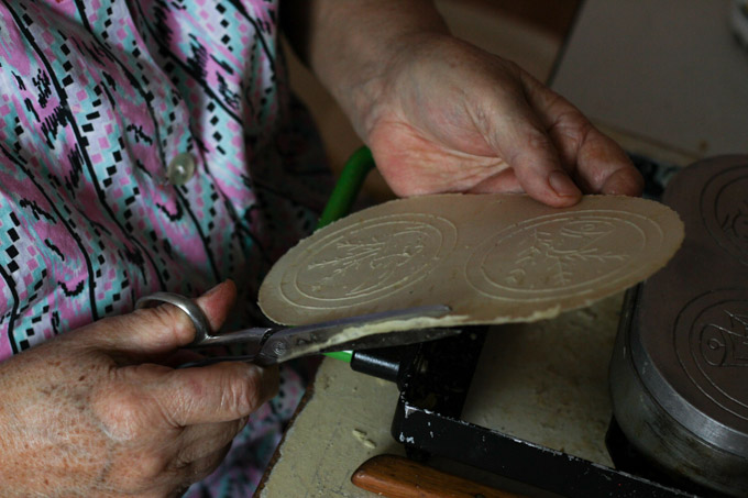 A Slovak woman trims a Christmas wafer