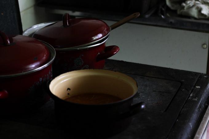 Enamel pots sit atop a wooden cook stove