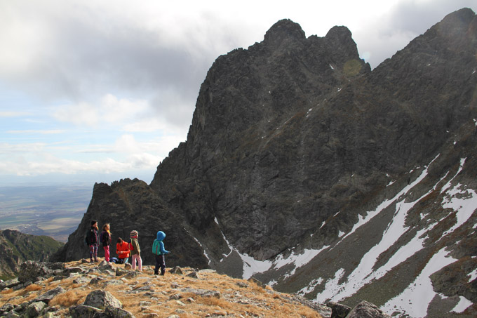 A family considers the views with Prostredny hrot in the background. High Tatra mountains, Slovakia.
