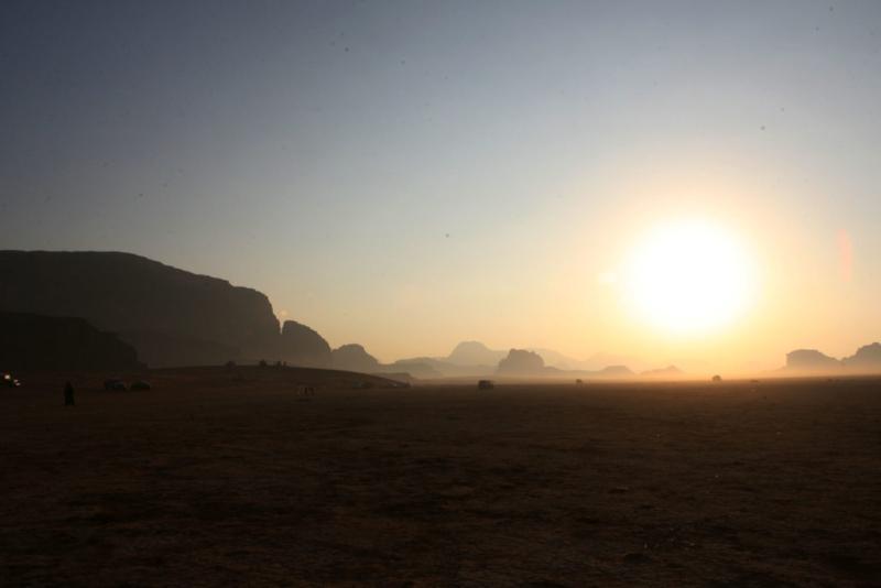 """غروب الشمس الناعسة في الأفق ينسدل برفق على أعالي سفوحها.. رمالٌ مستلقيةٌ وأخرى متواريةٌ خلف جبال عاتية.. نسيمٌ معطرٌ عليل.. ليلٌ يعانق النجوم في سمائها. إنها صحراء """"وادي رم"""" بالأردن التي تسحر زائرها بجمالها غير التقليدي، وتأخذه ممتطياً إِبلها في رحلة تظل خباياها وعشقها في الذاكرة، ليعود إليها كلما قادته الأقدار. جمالٌ يجعل يأس الزائر يجف على باب الطبيعة الموصود، ويستسلم إلى أوتار لحنها. فتلك راويةٌ تسير بالماء في إناء فوق رأسها فيتناثر بعضه على ملابسها وهي تحث الخطى إلى خيمتها.. وهذه ناقة حارسة على الباب. (ارشيف) ( Salah Malkawi - وكالة الأناضول )"""